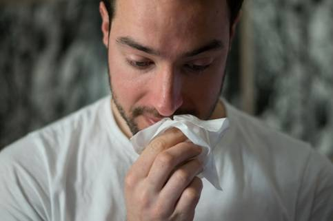 A man down with flu holding tissue.