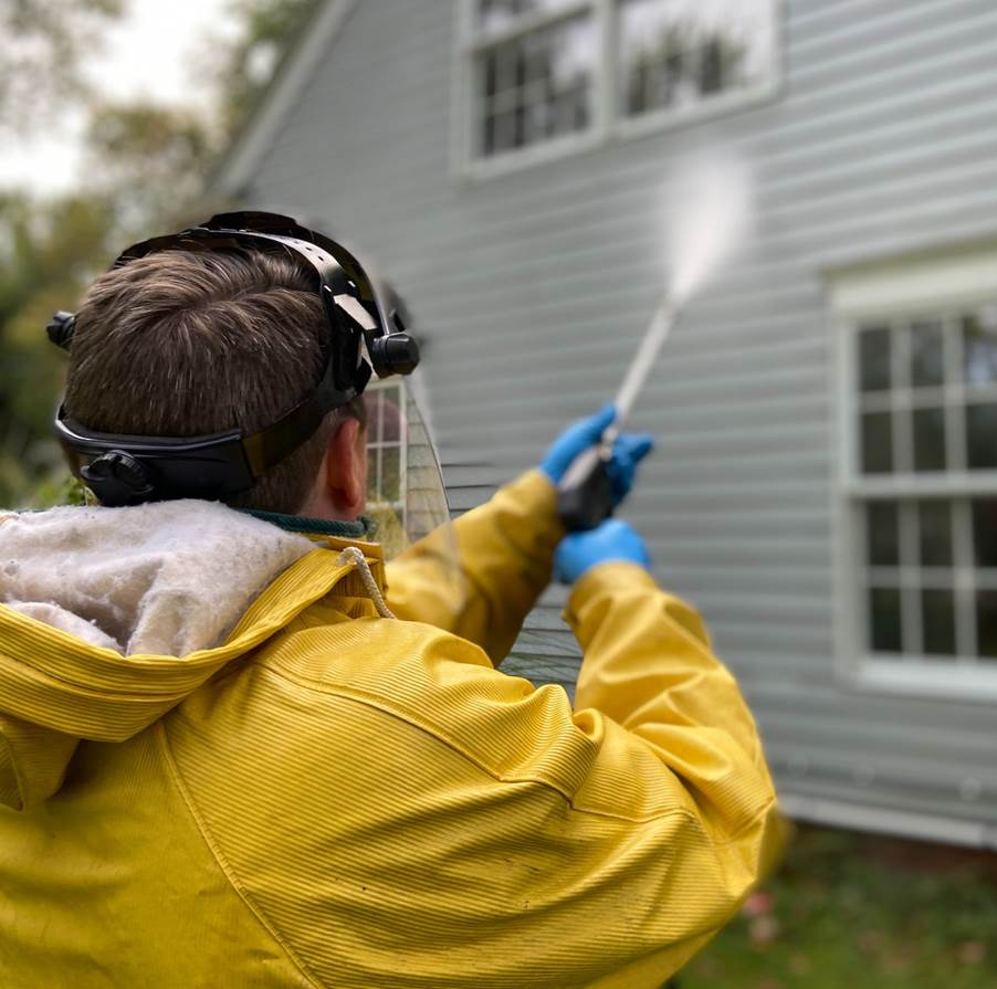 A professional power-washing the exterior of a house
