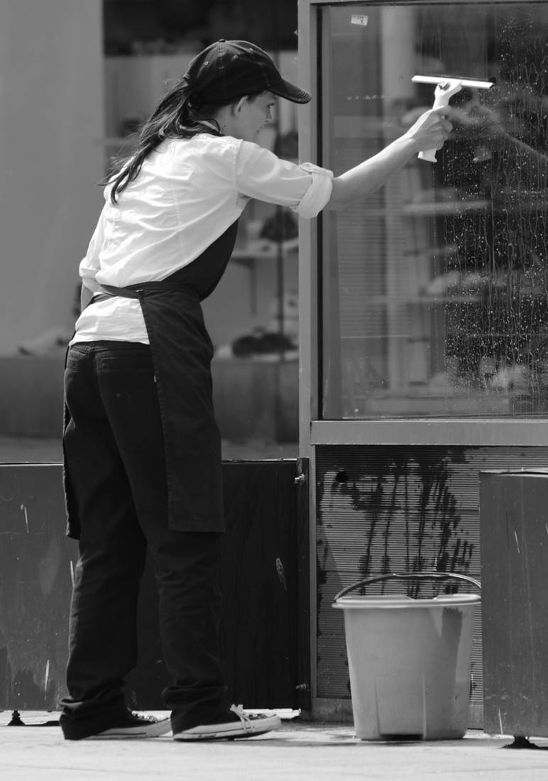 A professional window cleaner washing windows of a store front